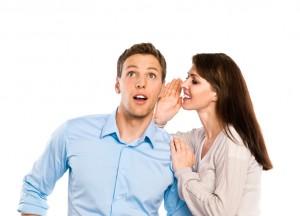 Frau flüstert Mann ins Ohr